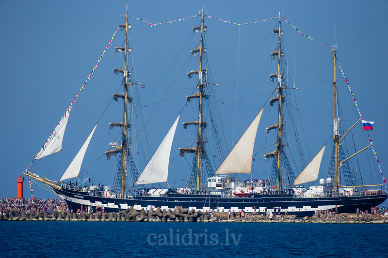 People on the mole of port Riga watch as last of the larges ships of Tall Ships Race 20013 Kruzenshtern leaves Riga