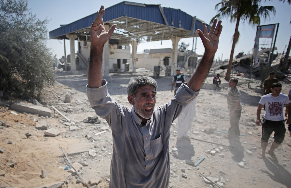 . A Palestinian man reacts after seeing the ruins of houses caused by Israeli strikes in the village of Khuzaa, southern Gaza Strip, close to the Israeli border, Friday, Aug. 1, 2014. A three-day Gaza cease-fire that began Friday quickly unraveled, with Israel and Hamas accusing each other of violating the truce. (AP Photo/Khalil Hamra)