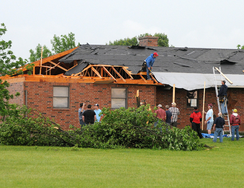 . Friends and neighbors help out a resident in Lyon County just south of Emporia, Kan., Sunday evening, May 19, 2013 after an apparent tornado touched down. (AP Photo/Emporia Gazette, Matthew Fowler)