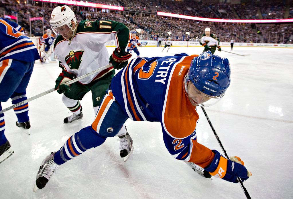 . Minnesota Wild\'s Torrey Mitchell (17) checks Edmonton Oilers\' Jeff Petry during the first period of an NHL hockey game Thursday, Feb. 21, 2013, in Edmonton, Alberta. (AP Photo/The Canadian Press, Jason Franson)