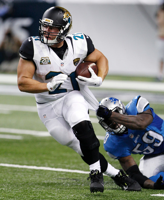 . Jacksonville Jaguars running back Toby Gerhart (21) is brought down from behind by Detroit Lions linebacker Tahir Whitehead (59) in the second half of a preseason NFL football game at Ford Field in Detroit, Friday, Aug. 22, 2014.  (AP Photo/Duane Burleson)
