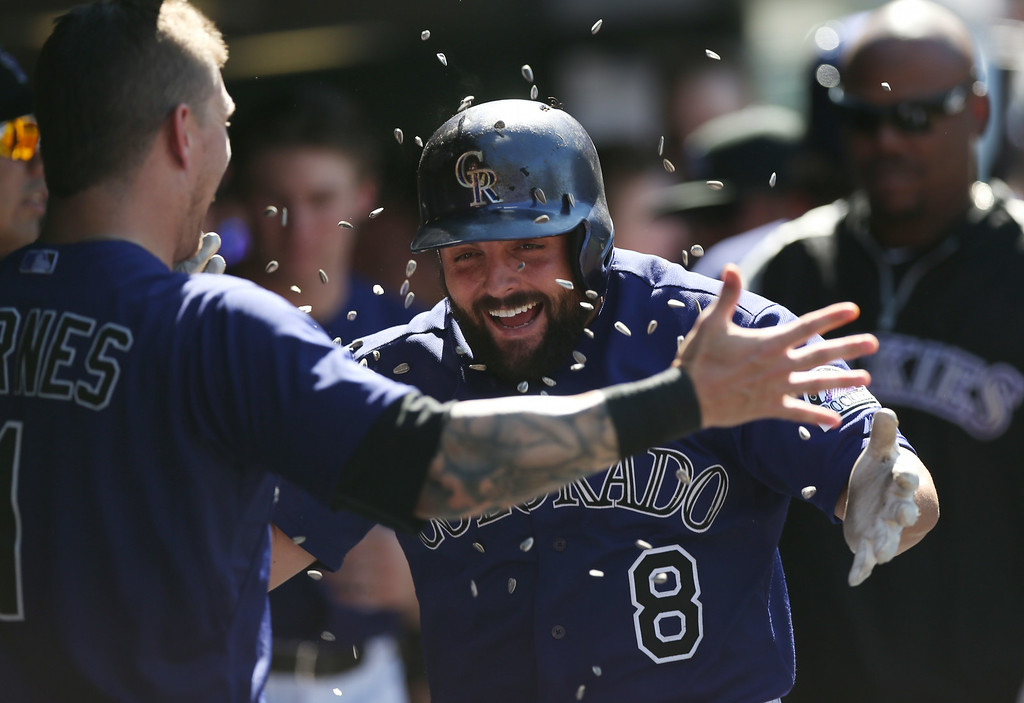 . Colorado Rockies\' Brandon Barnes, front, tosses a handful of sunflower seeds at Michael McKenry who returns to the dugout after hitting a solo home run in the sixth inning of their 9-2 victory in a baseball game against the San Francisco Giants in Denver, Wednesday, Sept. 3, 2014. (AP Photo/David Zalubowski)