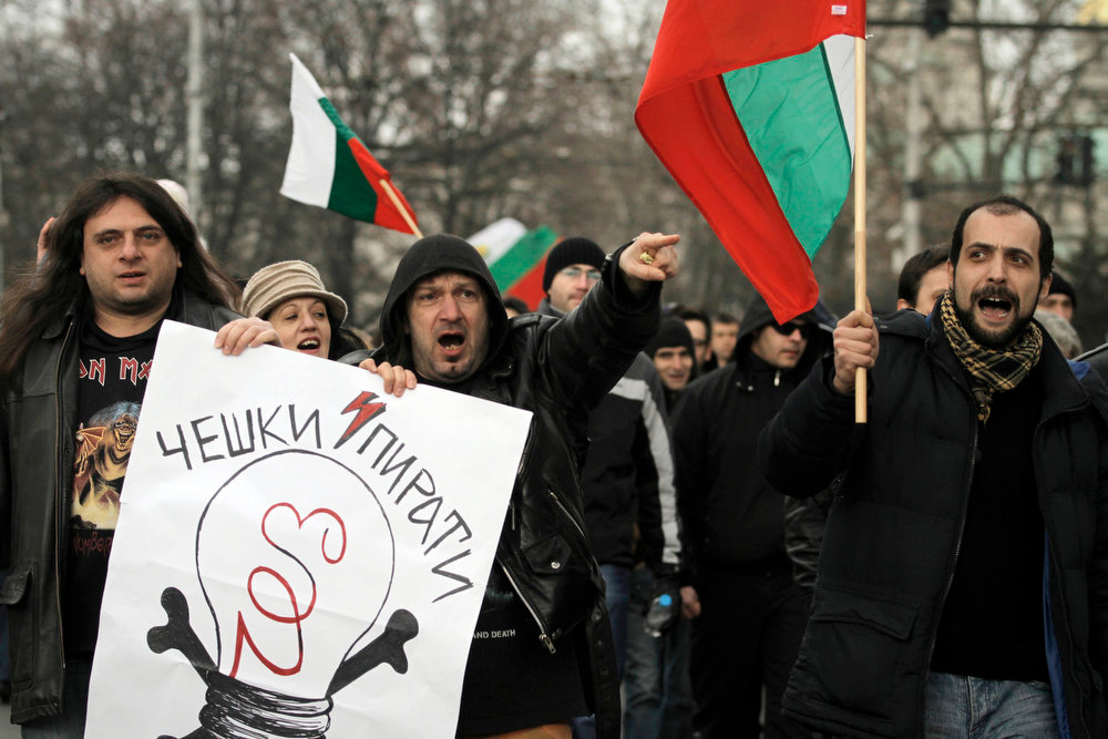 ". Bulgarians shout slogans and carry poster reading ""CEZ - Czech pirates\"" as they protest against higher electricity and heating bills, in Sofia,  Sunday, Feb. 17, 2013. Thousands of angry Bulgarians chanted \""mafia\"" and \""resignation\""  demanded the expulsion of the three foreign-controlled power distributors that control the local market: Czech Republic\'s CEZ and Energo-Pro, and Austria\'s EVN   (AP Photo/Valentina Petrova)"