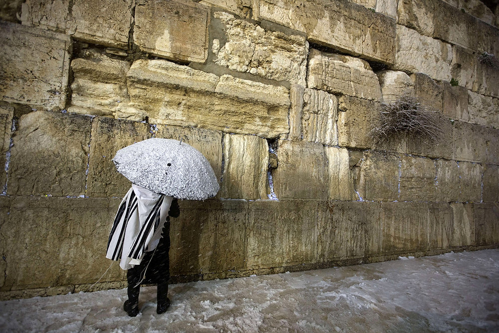 Description of . A Jewish man holding a snow-covered umbrella prays at the Western Wall in the old city of Jerusalem on January 10, 2013. Jerusalem was transformed into a winter wonderland after heavy overnight snowfall turned the Holy City and much of the region white, bringing hordes of excited children onto the streets. MENAHEM KAHANA/AFP/Getty Images