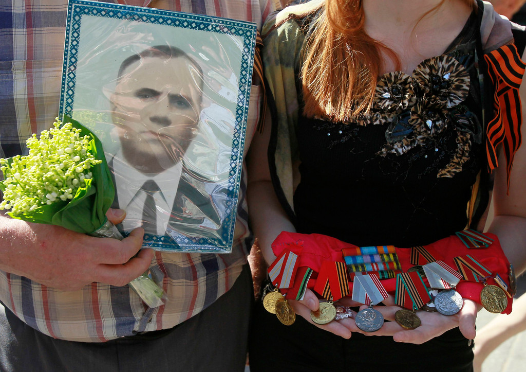""". People holding a portrait and medals of their relative who died after World War Two march in an improvised \""""Victory Day march\"""" to pay homage to their loved ones in Kiev May 9, 2013. Ukraine commemorates the 68th anniversary of the Soviet Union\'s victory over Nazi Germany on May 9.  REUTERS/Gleb Garanich"""