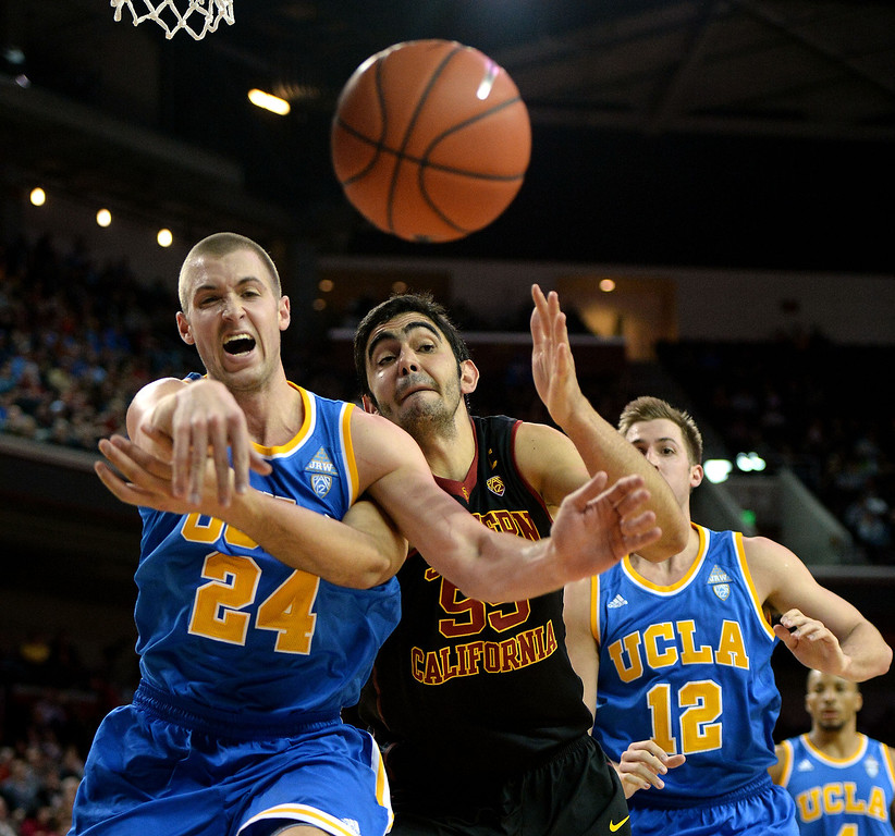 . UCLA\'s Travis Wear (24) scrambles for the loose ball with Southern California\'s Omar Oraby (55) as David Wear (12) looks on in the second half of a PAC-12 NCAA basketball game at Galen Center in Los Angeles, Calif., on Saturday, Feb. 8, 2014. UCLA won 83-73. (Keith Birmingham Pasadena Star-News)