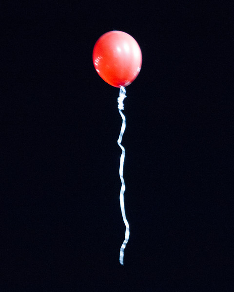 A lost red balloon floats away