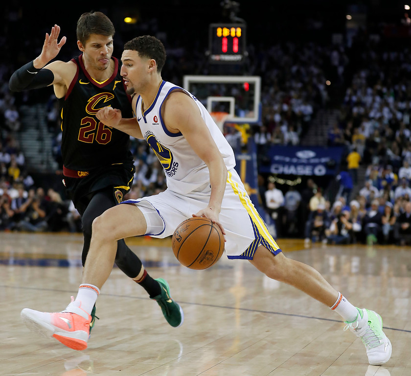 . Golden State Warriors guard Klay Thompson (11) drives to the basket against Cleveland Cavaliers guard Kyle Korver (26) during the second half of an NBA basketball game in Oakland, Calif., Monday, Dec. 25, 2017. The Warriors won 99-92. (AP Photo/Tony Avelar)