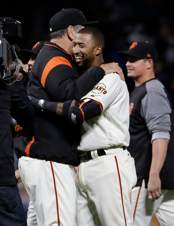 . San Francisco Giants\' Eduardo Nunez, front right, hugs manager Bruce Bochy after singling to score Kelby Tomlinson for the winning run during the 10th inning of a baseball game against the Cleveland Indians in San Francisco, Tuesday, July 18, 2017. The Giants won 2-1. (AP Photo/Jeff Chiu)
