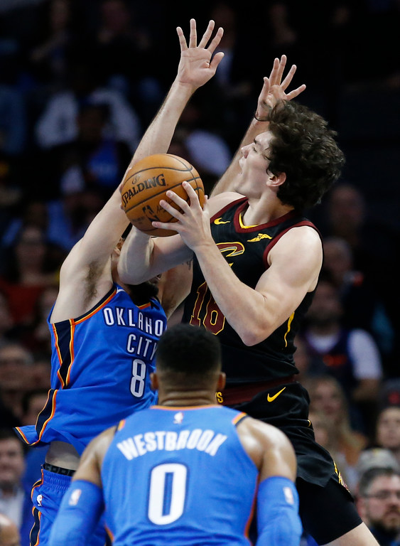 . Cleveland Cavaliers forward Cedi Osman, right, goes to the basket in front of Oklahoma City Thunder guard Alex Abrines, left rear, during the second half of an NBA basketball game in Oklahoma City, Tuesday, Feb. 13, 2018. (AP Photo/Sue Ogrocki)