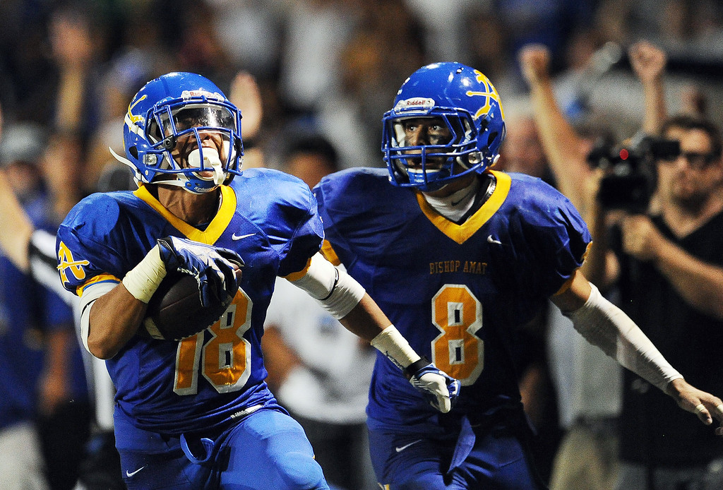 . Bishop Amat\'s Trevon Sidney (18) recovers a Santa Margarita fumble and runs back for a touchdown as teammate Michael Gonzales (8) looks on in the second half of a prep football game at Bishop Amat High School on Friday, Aug. 30, 2013 in La Puente, Calif. Bishop Amat won 38-28.   (Keith Birmingham/Pasadena Star-News)