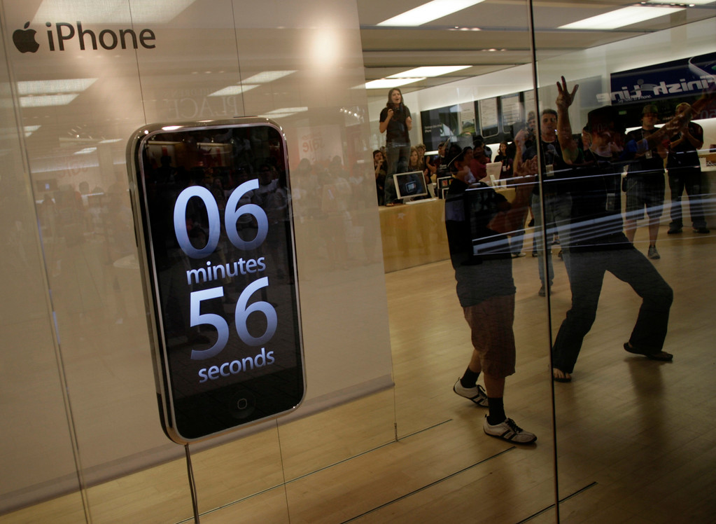 . Employees dance as the time clock ticks down for sale of the much-ballyhooed Apple  iPhone in the window of the Apple store in the tony Cherry Creek Mall in east Denver on Friday, June 29, 2007.  Some of the purchasers spent hours in line for a chance to get the much-ballyhooed phone. (AP Photo/David Zalubowski)
