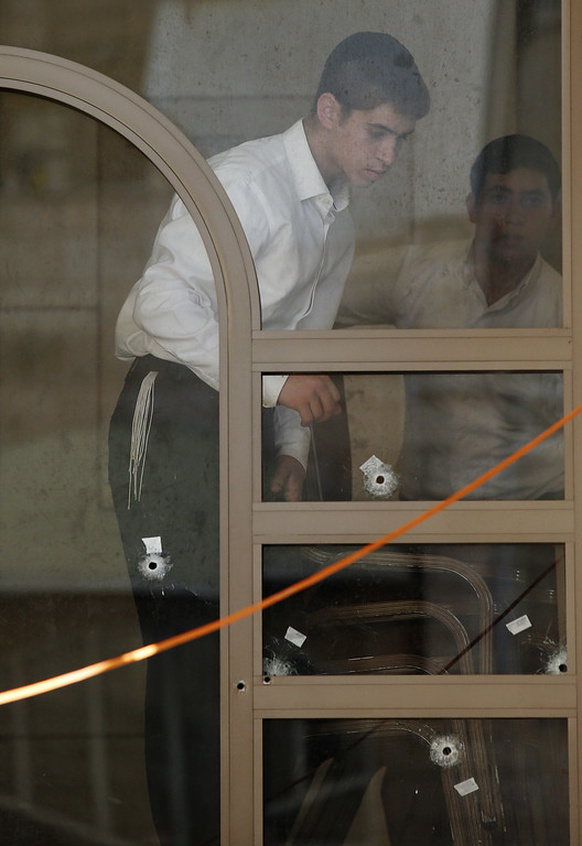 . Ultra-orthodox Jewish boys look at bullet holes in a window inside a synagogue that was attacked by two Palestinians earlier in the morning in the ultra-Orthodox Har Nof neighborhood in Jerusalem on November 18, 2014. AFP PHOTO/ JACK  GUEZ/AFP/Getty Images