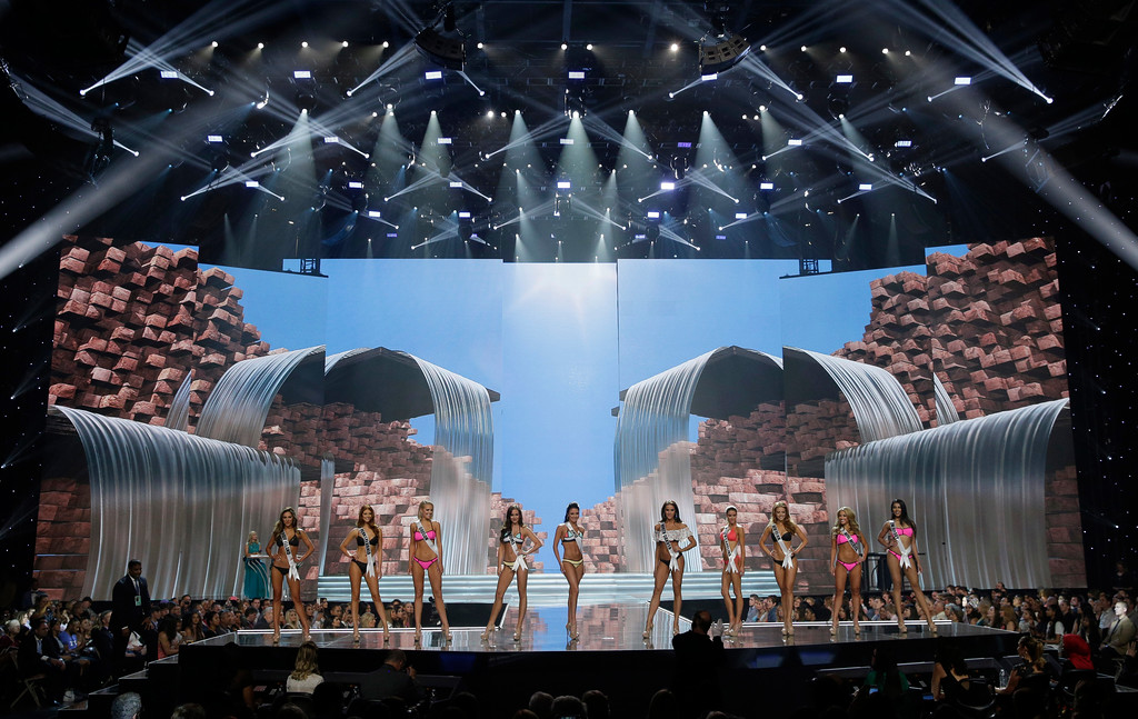 . In this May 11, 2017, photo, People including Miss North Dakota USA Raquel Wellentin, center right, compete during a preliminary competition for Miss USA in Las Vegas. Wellentin emigrated from the Philippines. Five of the contestants vying for the Miss USA title this year were born in other countries and now U.S. citizens. (AP Photo/John Locher)