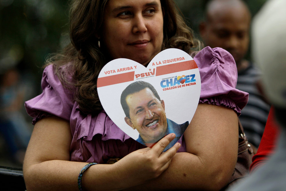 Description of . A supporter of Venezuela's President Hugo Chavez holds a heart-shaped placard with his image in Bolivar Square, where supporters gathered to celebrate his return, in Caracas, Venezuela, Monday, Feb. 18, 2013. Chavez returned to Venezuela early Monday after more than two months of medical treatment in Cuba following cancer surgery. Vice President Nicolas Maduro said on television that Chavez arrived at 2:30 a.m. and was taken to the Carlos Arvelo Military Hospital in Caracas, where he will continue his treatment. (AP Photo/Fernando Llano)