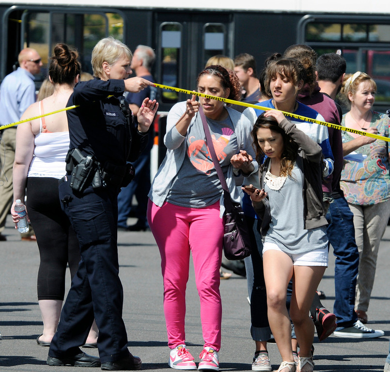 . A police officer lifts up police tape as students are arrive by bus to meet their parents and/or family at the Fred Meyer grocery store parking lot in Wood Village, Ore., after a shooting at Reynolds High School Tuesday, June 10, 2014, in nearby Troutdale.  (AP Photo/Greg Wahl-Stephens)