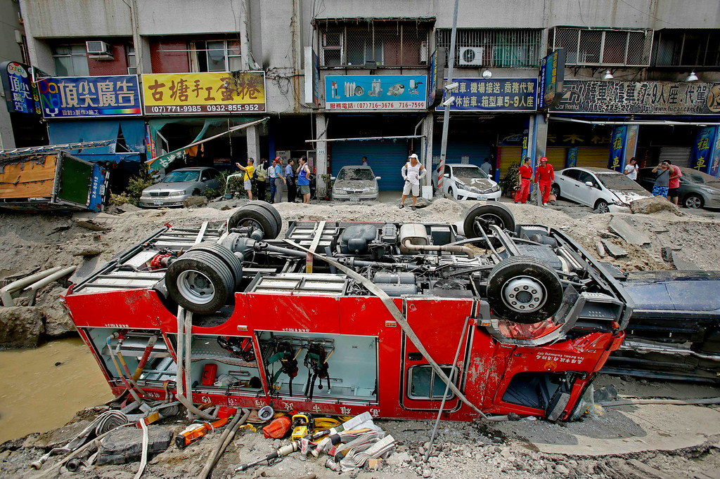 . A destroyed fire truck is seen overturned in the rubble after massive gas explosions in Kaohsiung, Taiwan, Friday, Aug. 1, 2014. A series of underground explosions about midnight Thursday and early Friday ripped through Taiwan\'s second-largest city, killing scores of people, Taiwan\'s National Fire Agency said Friday. (AP Photo/Wally Santana)