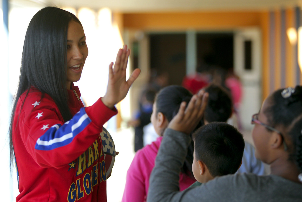 """. Harlem Globetrotters� rookie and Oakland native Tammy �T-Time� Brawner high fives students following a visit by her and teammate Slick Willie Shaw were the two presented the team\'s \""""ABC\'s of Bullying Prevention\"""" program at Laurel Elementary School in Oakland, Calif., on Wednesday, Jan. 16, 2013. (Anda Chu/Staff)"""
