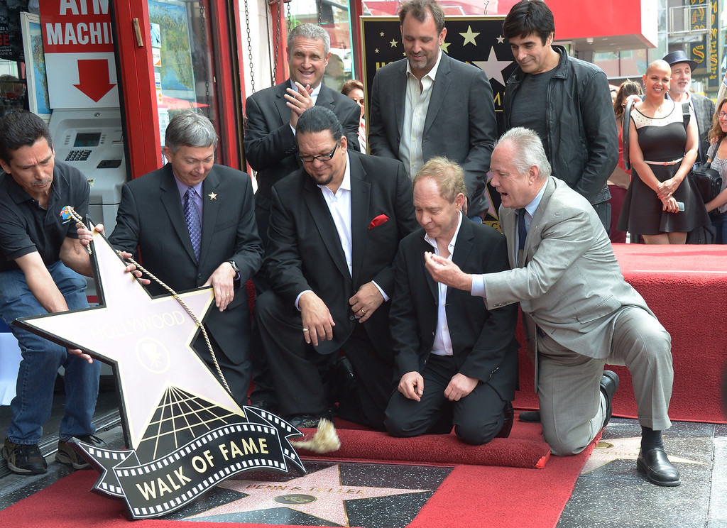 . American illusionists and entertainers Penn Jillette (C) and Teller (C, R) are honored with a star on the Hollywood Walk of Fame on April 05, 2013 in Hollywood, California. AFP PHOTO/JOE KLAMAR        (Photo credit should read JOE KLAMAR/AFP/Getty Images)