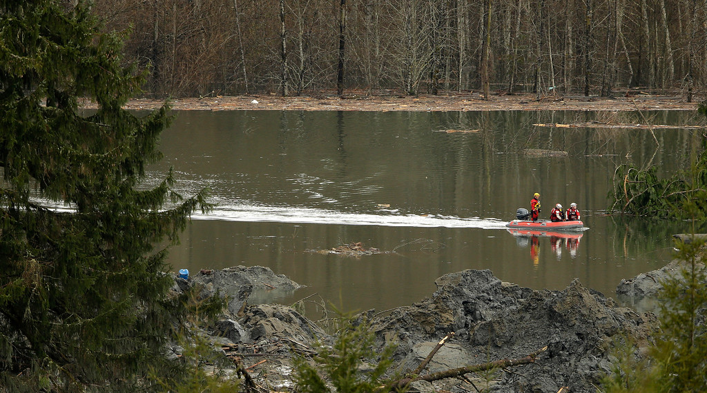 . Search and rescue workers use a boat to move around Thursday, March 27, 2014, in as they search through mud and debris from the massive mudslide that struck Saturday near Darrington, Wash. (AP Photo/Ted S. Warren, Pool)