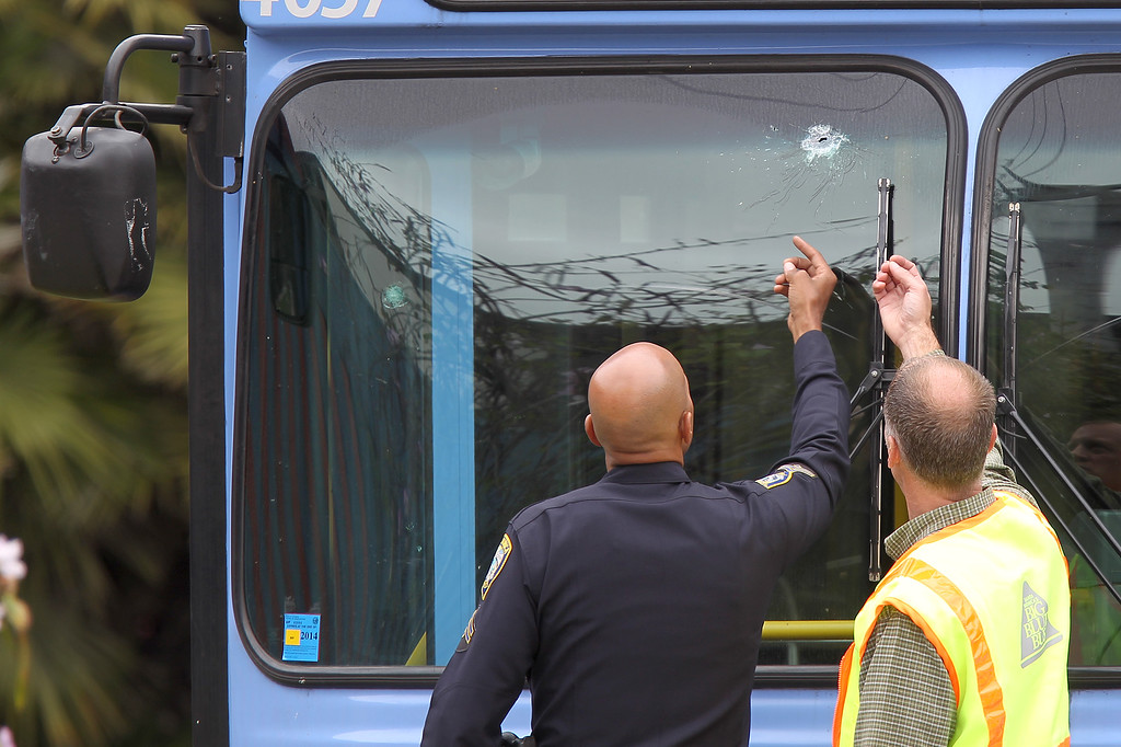 . SANTA MONICA, CA - JUNE 07:  A police officer and a transit official look at a bullet hole, one of many, in a public transit bus in which two passengers were shot, after multiple shootings were reported at various locations including Santa Monica College June 7, 2013 in Santa Monica, California. According to reports, at least six people have died in the shootings.  (Photo by David McNew/Getty Images)