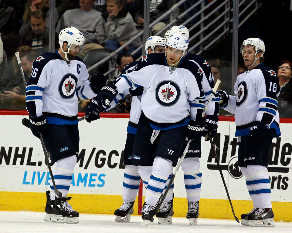 . Winnipeg Jets right wing Blake Wheeler, center, celebrates his power play goal with left wing Andrew Ladd, left, and center Bryan Little (18) against the Colorado Avalanche in the second period of an NHL hockey game in Denver on Sunday, Oct. 27, 2013. (AP Photo/David Zalubowski)