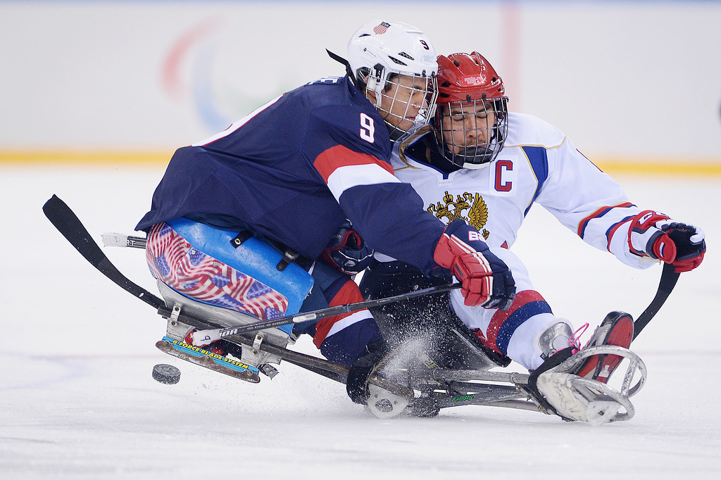 . Andy Yohe of the United States and Dmitrii Lisov of Russia battle for the puck during the Ice Sledge Hockey Preliminary Round Group B match between the United States of America and Russia during day four of Sochi 2014 Paralympic Winter Games at Shayba Arena on March 11, 2014 in Sochi, Russia.  (Photo by Dennis Grombkowski/Getty Images)