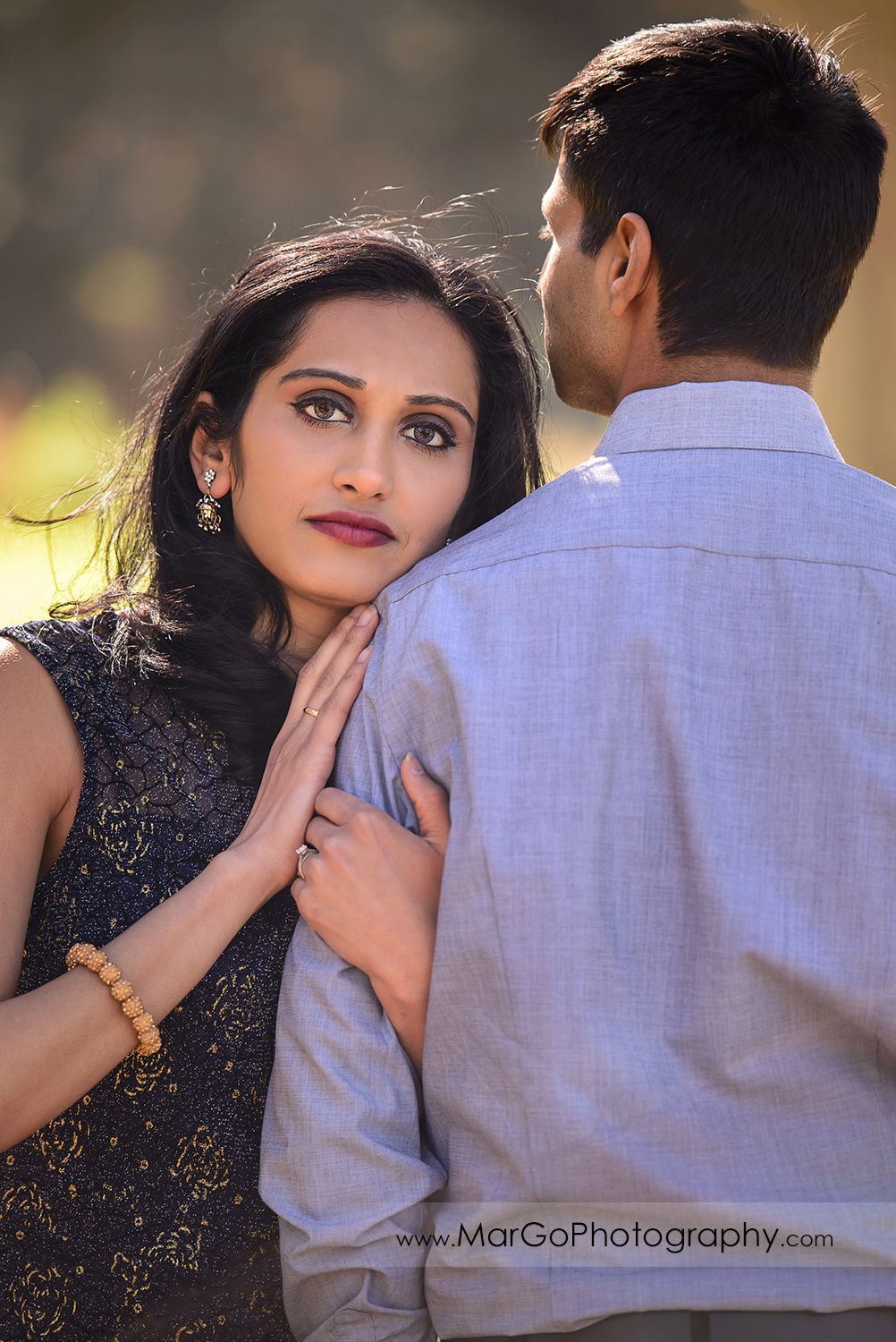 portrait of Indian woman in blue clothes holding hands on arm of the man in blue shirt during engagement session at San Francisco Presidio Park