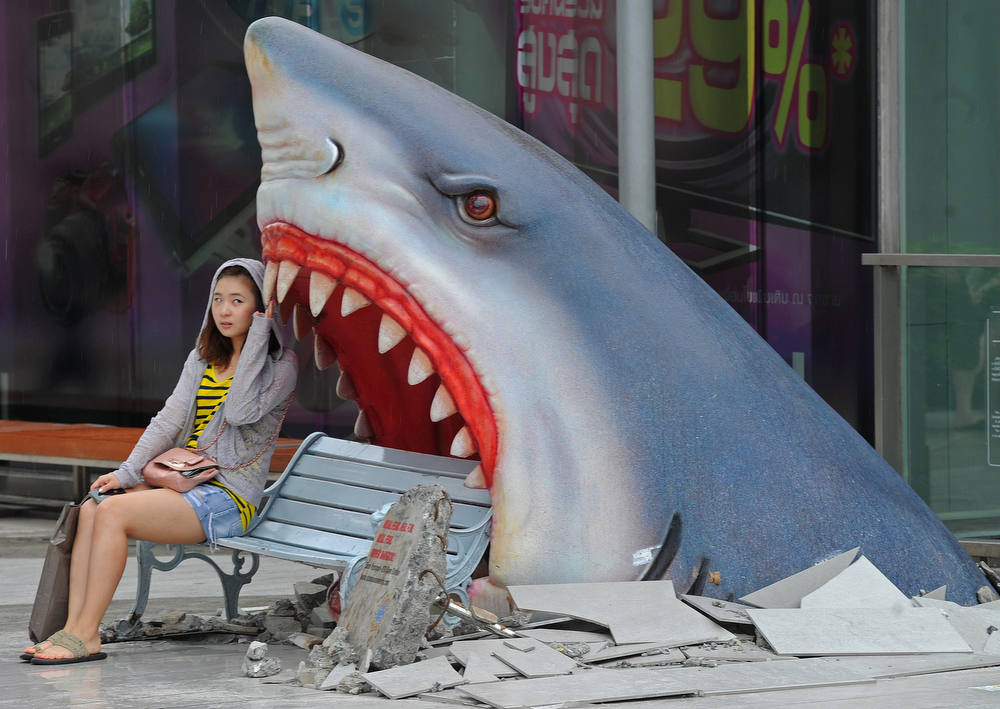 Description of . A foreign tourist sits next to a large art display of a shark displayed at a shopping mall in Bangkok on July 9, 2012.  Thailand is a tourist magnet but its image as the