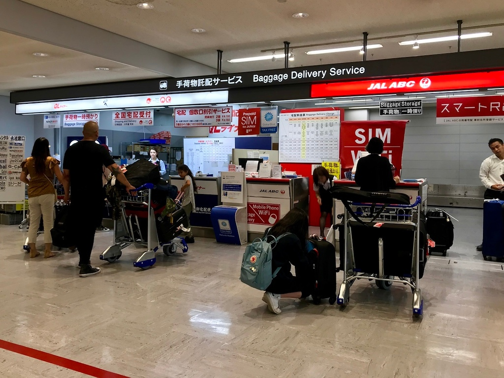 Two of many baggage delivery service counters in Narita Airport.