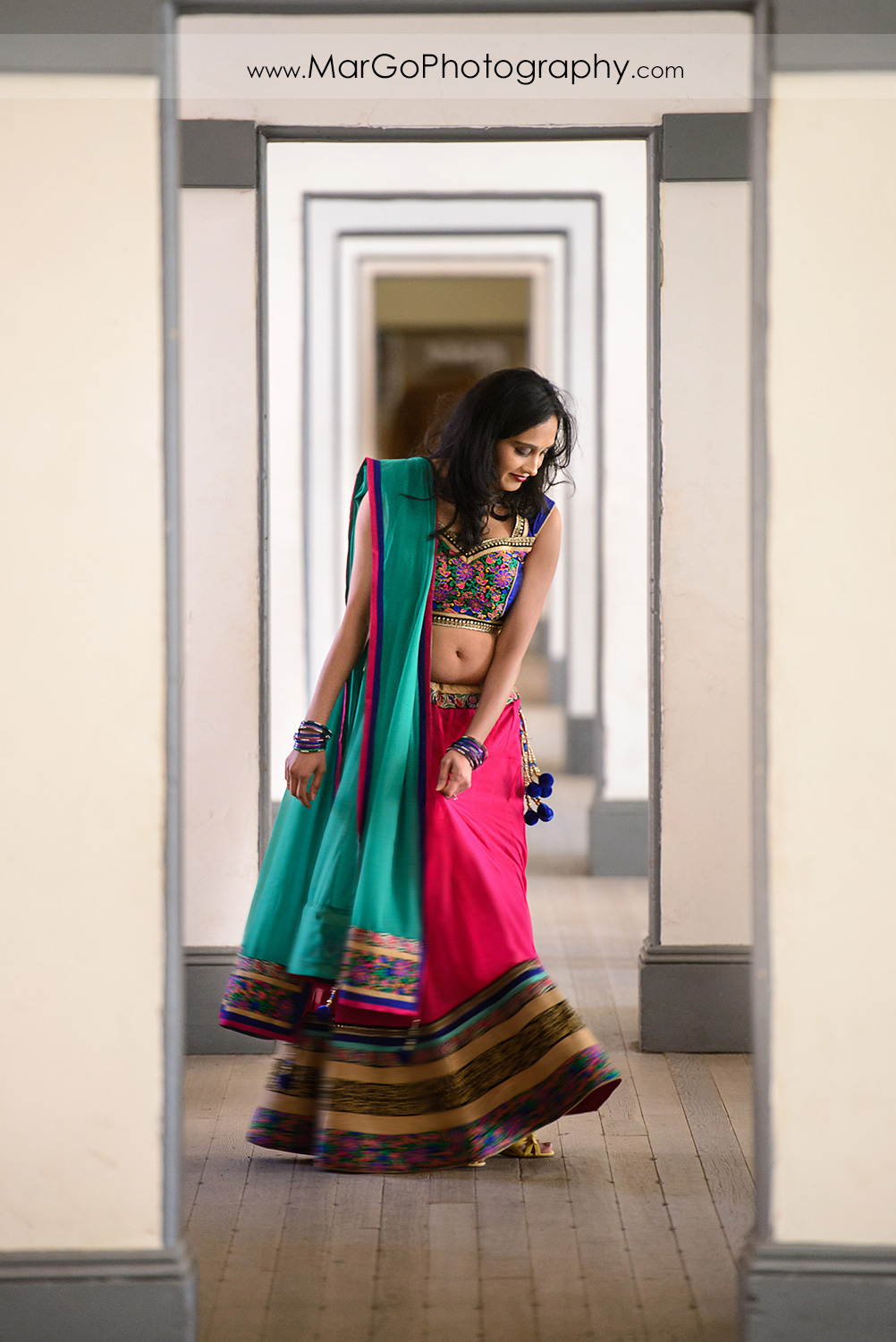 portrait of Indian woman in pink and green dress in the white hallway during engagement session at San Francisco Fort Point