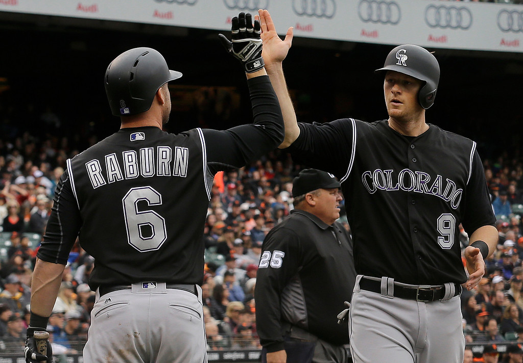 . Colorado Rockies\' DJ LeMahieu (9) is congratulated by Ryan Raburn after scoring against the San Francisco Giants during the tenth inning of a baseball game in San Francisco, Saturday, May 7, 2016. (AP Photo/Jeff Chiu)