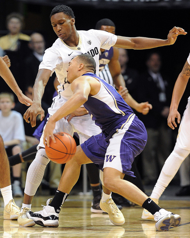. Andrew Andrews of Washington runs into Jaron Hopkins of Colorado during the first half of the February 9, 2014 game in Boulder, Colo.   (Cliff Grassmick /Daily Camera)