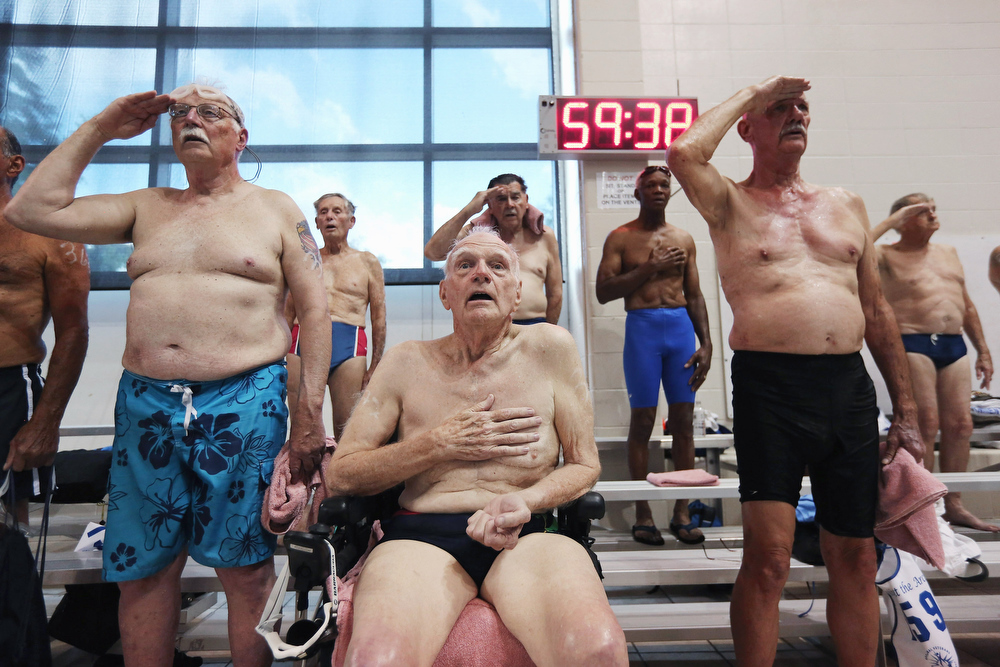 Description of . Senior military veterans, including World War II veteran Wayne Field, 86, (C), sing the national anthem before the swimming competition at the National Golden Age Games on June 4, 2012 in St Peters, Missouri. Almost 800 veterans between the ages of 55 and 101 from around the United States participated in the annual six-day event held by the Departement of Veterans Affairs this year in the St Louis area. The veterans competed in a wide range of sporting and recreational events, from swimming to dominoes, many of which were qualifying events for the 2013 National Senior Games. (Photo by John Moore/Getty Images)