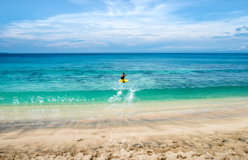 Skimboarding kid catching big air over waves of azure blue water