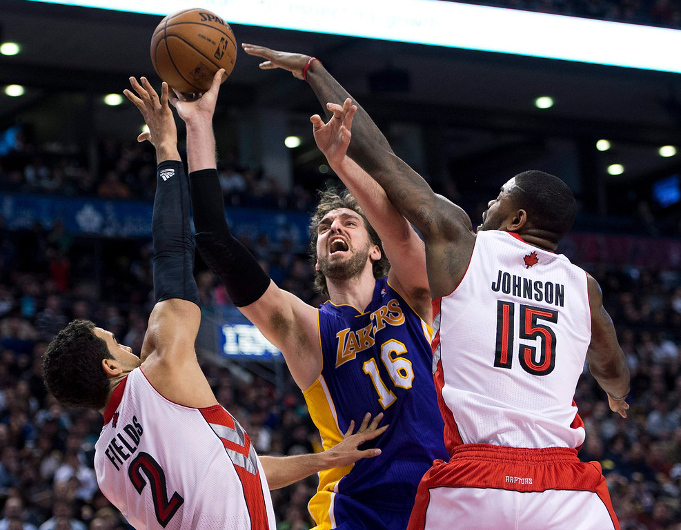 . Toronto Raptors\' Landry Fields (2) and Amir Johnson (15) battles for the ball against Los Angeles Lakers\' Pau Gasol (16) during the second half of an NBA basketball game, Sunday, Jan. 20, 2013, in Toronto. The Raptors won 108-103. (AP Photo/The Canadian Press, Nathan Denette)