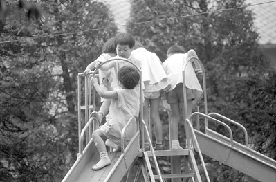 Kids at a local Japanese grade school having fun on the slides.  Tokyo 1965