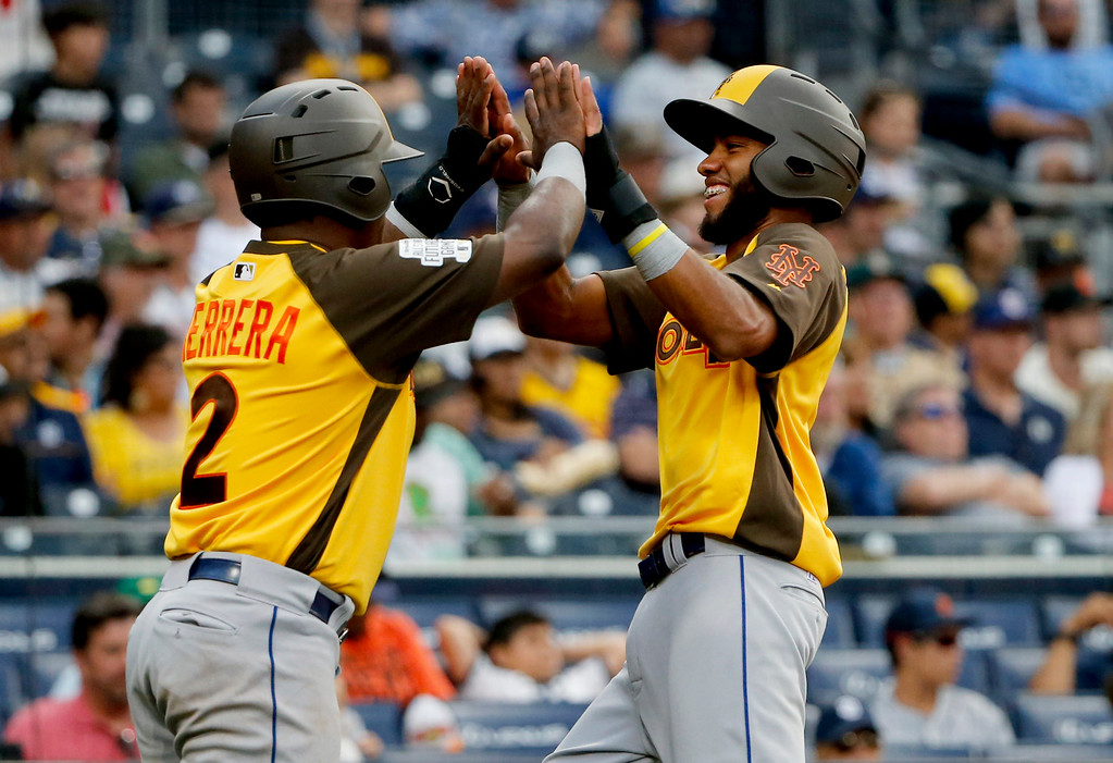 . World Team\'s Amed Rosario, of the New York Mets, right, high fives teamamte Dilson Herrera, of the New York Mets, after scoring on an RBI base hit by Raimel Tapia during the ninth inning of the All-Star Futures baseball game, Sunday, July 10, 2016, in San Diego. (AP Photo/Lenny Ignelzi)