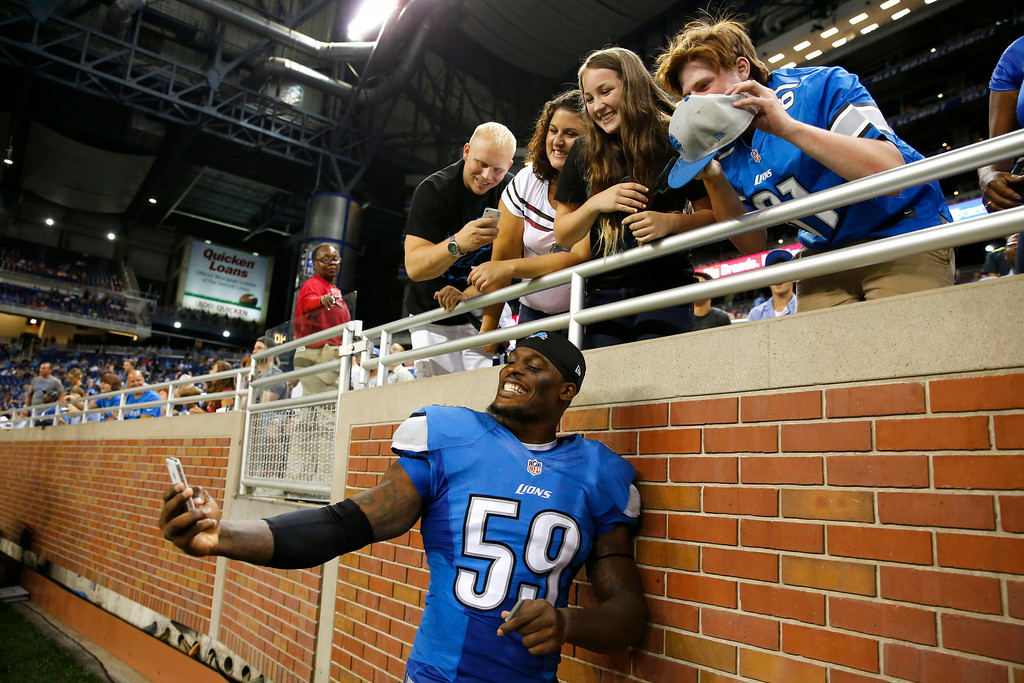 . Detroit Lions linebacker Tahir Whitehead (59) shoots a selfie with fans after a preseason NFL football game against the Jacksonville Jaguars at Ford Field in Detroit, Friday, Aug. 22, 2014. (AP Photo/Rick Osentoski)