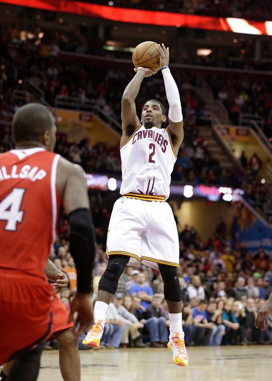 . Cleveland Cavaliers\' Kyrie Irving (2) shoots over Atlanta Hawks\' Paul Millsap (4) during an NBA basketball game Thursday, Dec. 26, 2013, in Cleveland. (AP Photo/Tony Dejak)