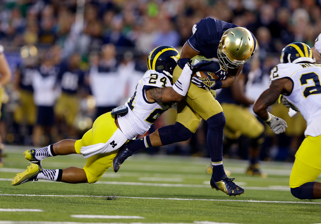 . Notre Dame wide receiver Amir Carlisle, right, is tackled by Michigan defensive back Delonte Hollowell during the first half of an NCAA college football game in South Bend, Ind., Saturday, Sept. 6, 2014. (AP Photo/Michael Conroy)