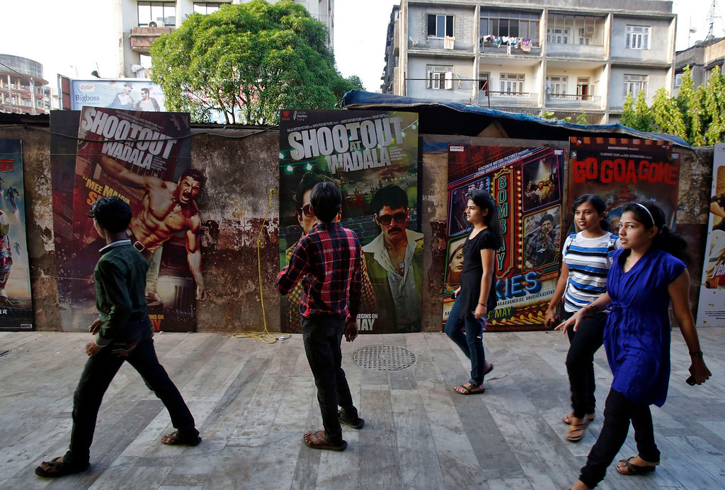 """. People walk past Bollywood film posters in Mumbai April 14, 2013. Indian cinema marks 100 years since Dhundiraj Govind Phalke\'s black-and-white silent film \""""Raja Harishchandra\"""" (King Harishchandra) held audiences spellbound at its first public screening on May 3, 1913, in Mumbai. Indian cinema, with its subset of Bollywood for Hindi-language films, is now a billion-dollar industry that makes more than a thousand films a year in several languages. It is worth 112.4 billion rupees (over $2 billion) and leads the world in terms of films produced and tickets sold. Picture taken April 14, 2013. REUTERS/Vivek Prakash"""