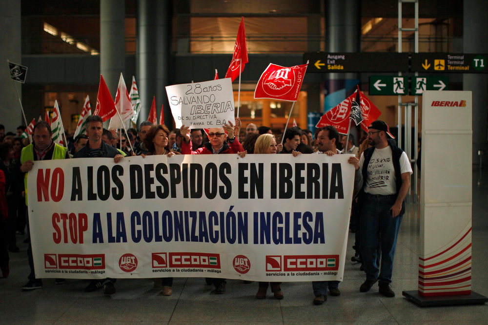 ". Iberia workers protest during a strike at Pablo Ruiz Picasso Airport in Malaga, southern Spain February 18, 2013. Striking union workers clashed with police at Madrid\'s Barajas airport on Monday on the first day of a week-long strike over more than 3,800 pending job cuts at Spain\'s flagship airline Iberia. The banner reads, ""No to layoffs in Iberia. Stop the British colonization\"", and the sign reads, \""28 years of protecting Iberia\'s policies, and now B.A. (British Airways)\"". REUTERS/Jon Nazca"