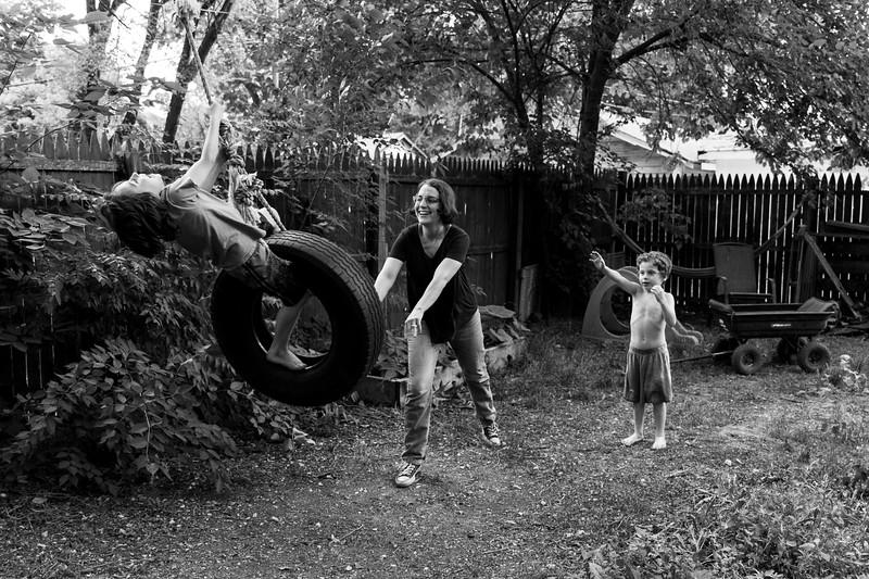 Mother pushing child on tire swing.JPG