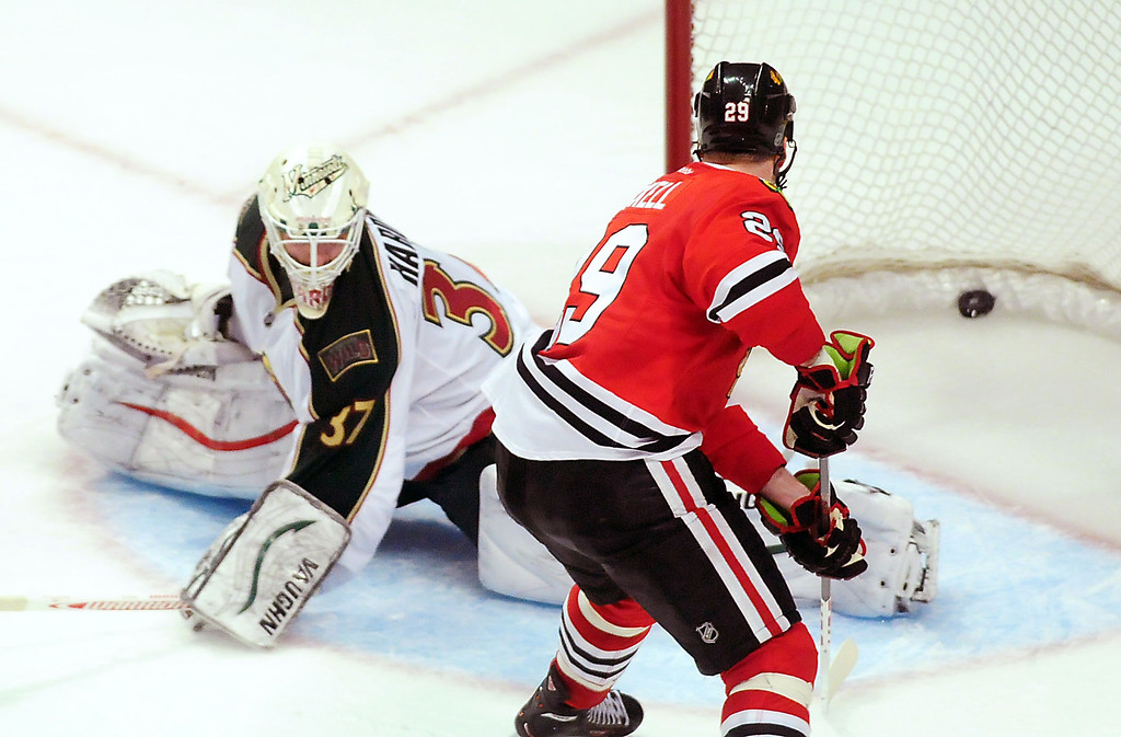 . Chicago\'s Bryan Bickell, left, scores the winning goal on Wild goalie Josh Harding to give Chicago a 2-1 win in overtime. (Pioneer Press: Ben Garvin)