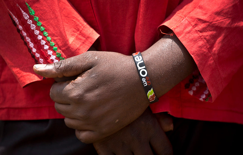 """. A member of the choir wears a wristband reading \""""We are one\"""", a message of national unity in the face of the Westgate Mall attack, as families of the victims and other well-wishers prepare to lay flowers and remember in the Karura Forest in Nairobi, Kenya Sunday, Sept. 21, 2014. Kenya is marking one year since four gunmen stormed the upscale Westgate Mall in Nairobi, killing 67 people, and a memorial plaque with the names of the victims was unveiled at the popular forest on the edge of the city. (AP Photo/Ben Curtis)"""