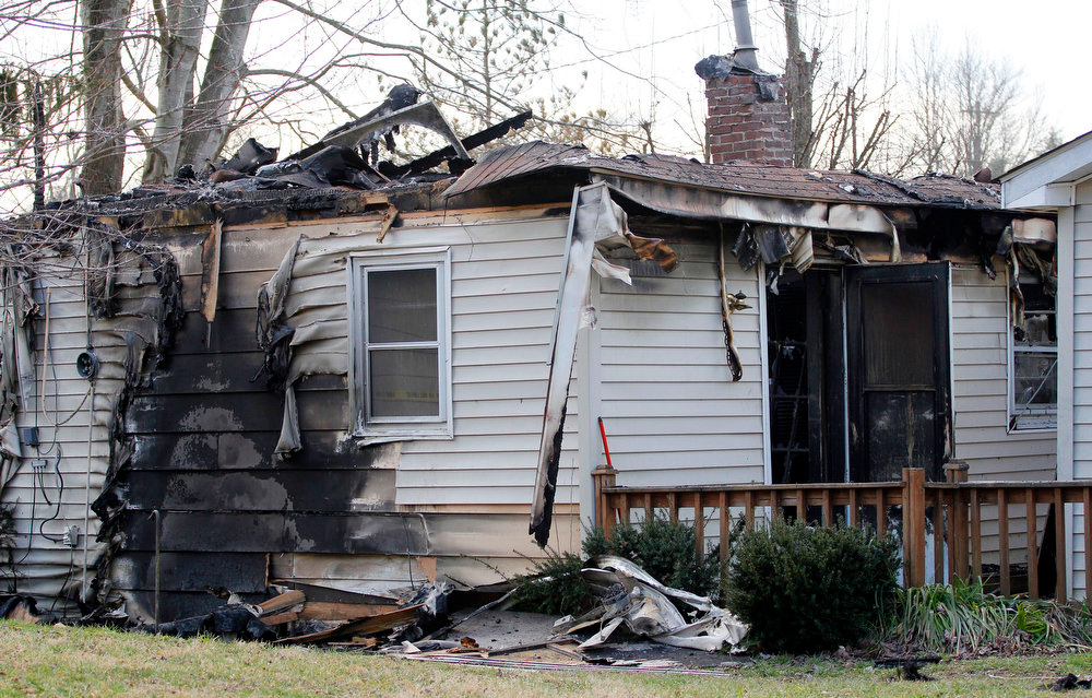 . This Sunday, March 10, 2013 photo shows the charred remains of a home after a fire erupted, Saturday, March 9, 2013 in Gray, Ky, killing two adults and five children inside. (AP Photo/Lisa Norman-Hudson)