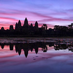 As the sun rises over Angkor Wat Temple, the skies light up with beautiful red and purple light.