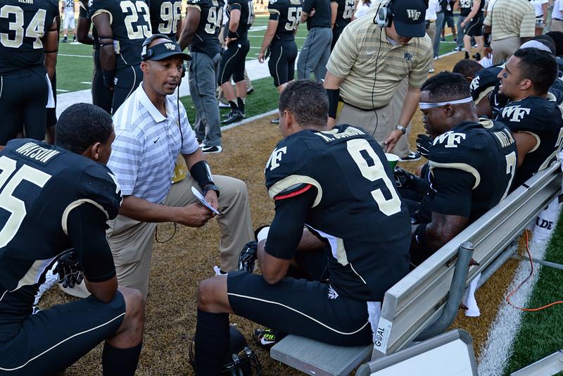 Coaches talk to defensive backs.jpg