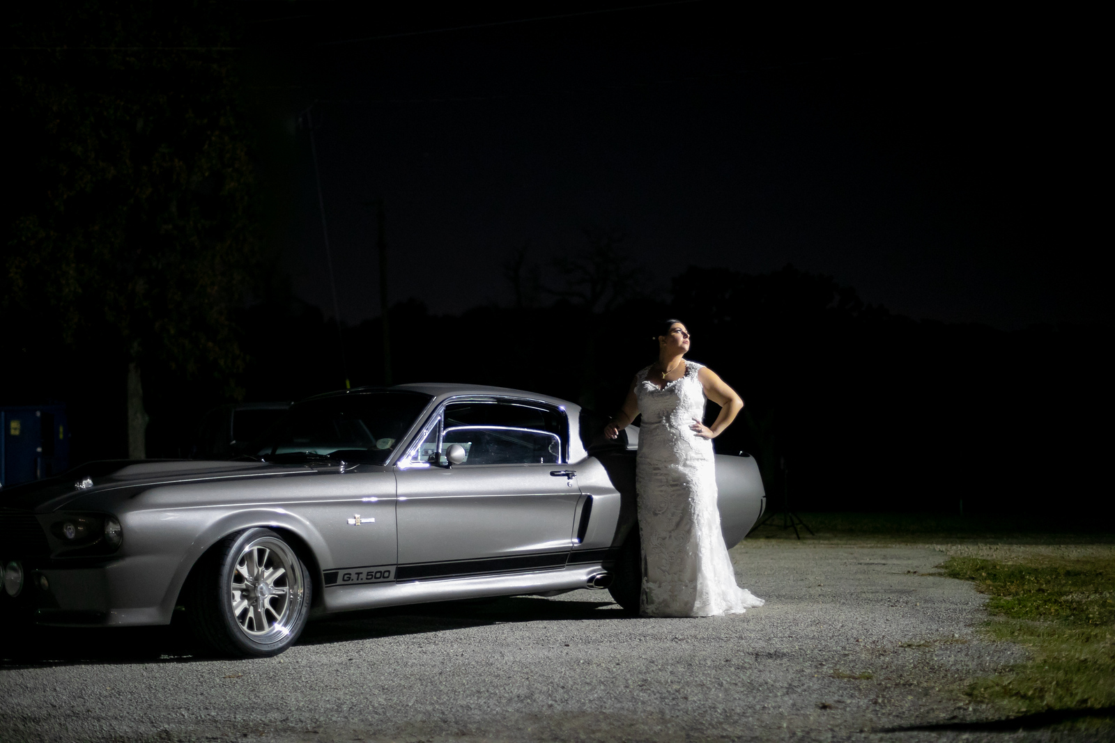 bride standing next to a Mustang on her wedding night